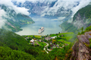 Norway cruise ship leaving a mountainous village port