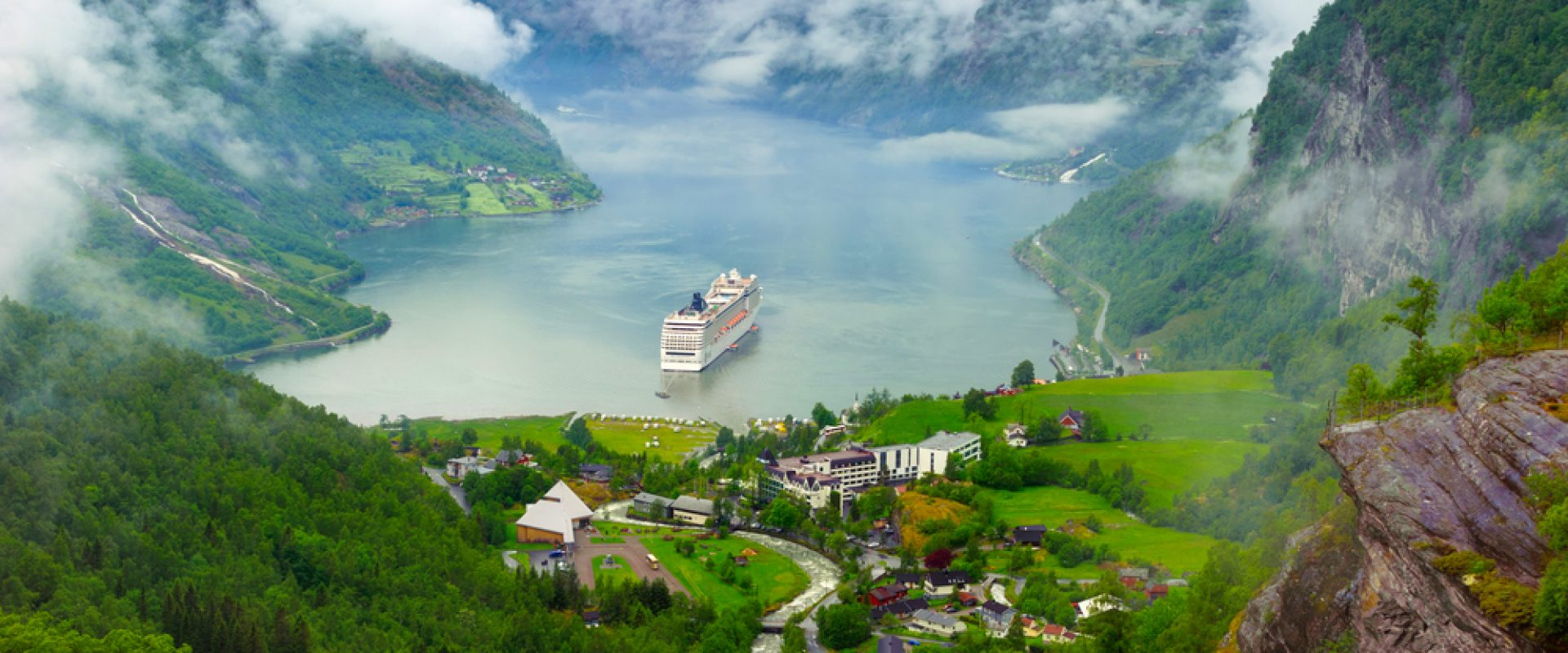 Norway cruise ship leaving a mountainous village port